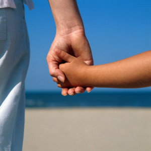 Woman and girl (6-8) on beach holding hands, close up